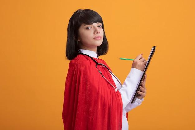 Junges superheldenmädchen, das stethoskop mit medizinischem gewand und umhang trägt, der etwas auf zwischenablage schreibt