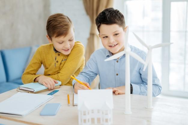 Junges talent. schöner jugendlicher junge, der neben seinem bruder am tisch sitzt und ihm beim besuch des büros ihres vaters beim zeichnen einer windkraftanlage zuschaut