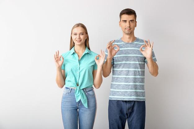 Junges taubstummes paar, das gebärdensprache auf weiß verwendet