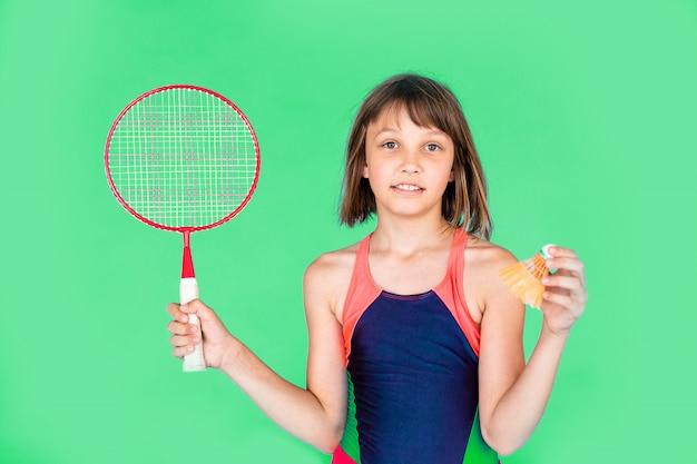 Junges teenager-mädchen, das badminton auf grüner wand springt und spielt