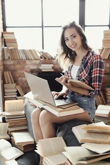 Junges teenager-mädchen, das den laptop-computer verwendet, der durch viele bücher umgeben wird.