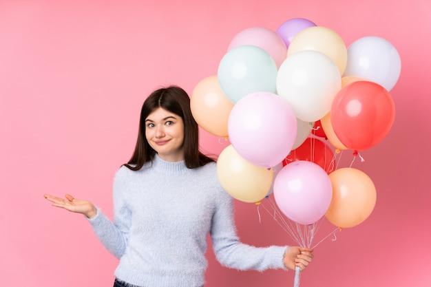 Junges teenager-mädchen, das viele luftballons über rosa wand hält, die zweifel mit verwirrtem gesichtsausdruck haben