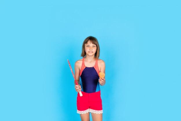 Junges teenager-mädchen springt und spielt badminton auf blauer wand