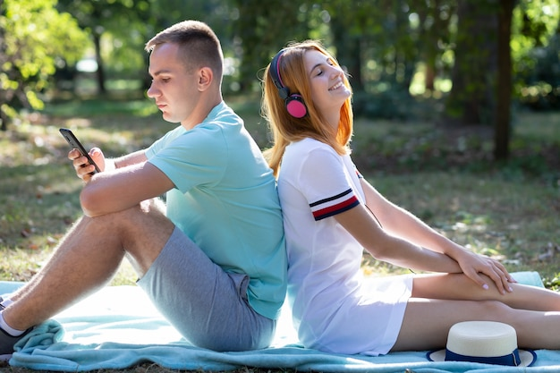 Junges teenagerpaar, das spaß draußen im sommerpark hat. mädchen mit roten haaren, die musik in rosa kopfhörern und jungen hören, die auf dem verkaufstelefon chatten.