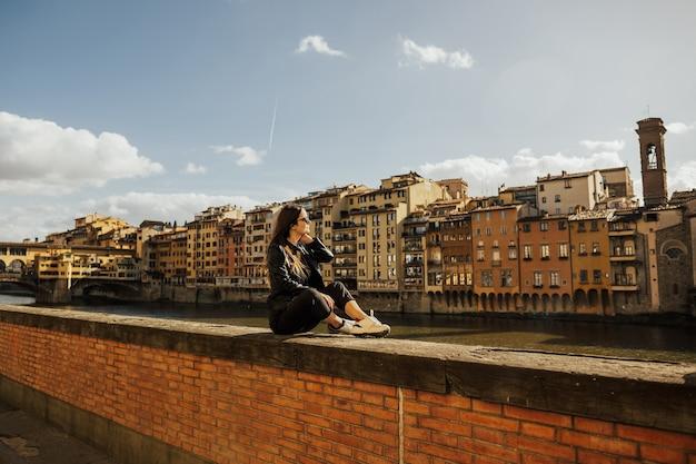 Junges touristenmädchen bei ponte vecchio ein mittelalterlicher stein