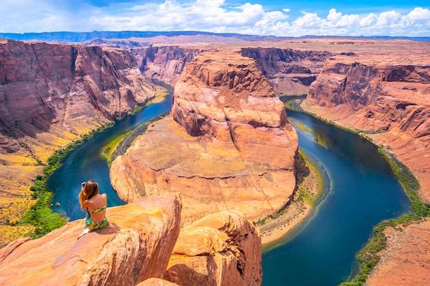 Junges touristenmädchen mit grünem kleid bei horseshoe bend beim fotografieren, arizona. vereinigte staaten