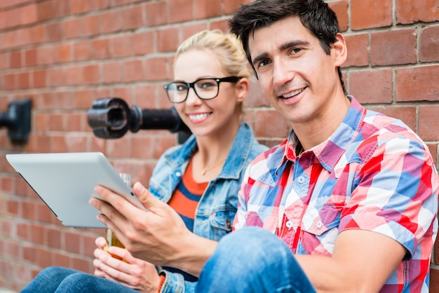 Junges touristenpaar, das online-stadtführer liest, bevor es rollertour in berlin macht
