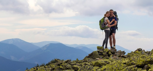 Junges touristenpaar mit rucksäcken, sportlichem mann und hübschem mädchen, das auf felsigem berggipfel auf nebligem bergpanoramahintergrund umarmt steht. tourismus-, reise-, kletter- und freundschaftskonzept.