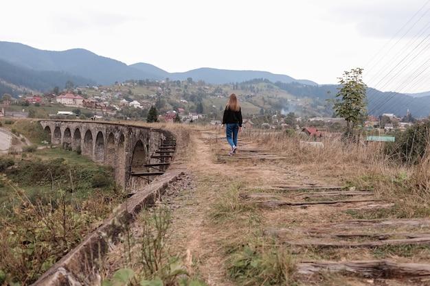 Junges touristisches mädchen geht die alten eisenbahnlinien auf dem viadukt. alter bahnviadukt im bergferienort vorokhta. ukraine, karpaten.