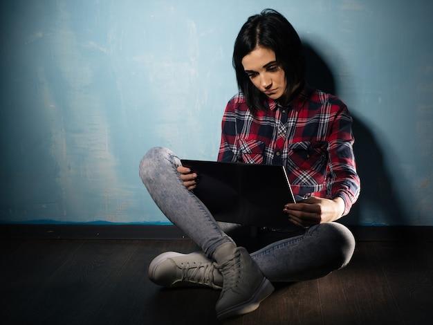 Junges trauriges mädchen, das unter der abhängigkeit von sozialen netzwerken leidet, die auf dem boden mit einem notizbuch sitzen