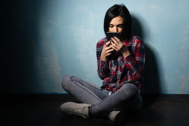 Junges trauriges mädchen, das unter der abhängigkeit von sozialen netzwerken leidet, die auf dem boden mit einem smartphone sitzen