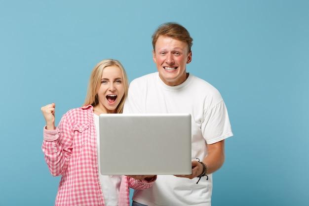 Junges überglückliches paar zwei freunde mann und frau in weißen rosa leeren leeren t-shirts posieren