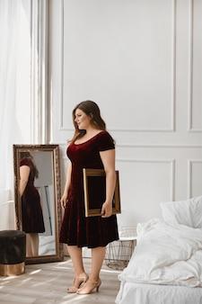 Junges übergroßes modellmädchen im roten samtkleid, das im studio aufwirft.
