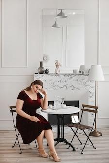 Junges übergroßes modellmädchen mit hellem make-up in einem roten samtkleid, das im wohnzimmerinnenraum aufwirft. xxl mode.