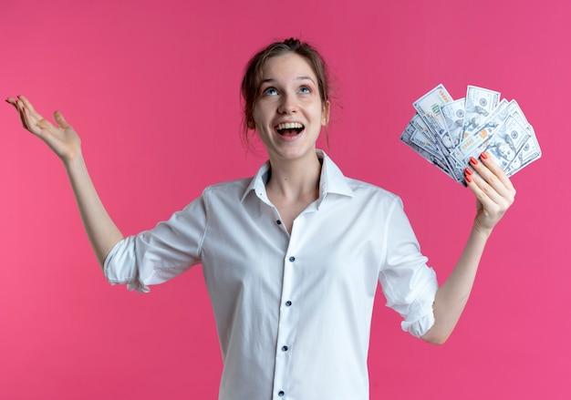 Junges überraschtes blondes russisches mädchen hält geld und erhebt hand, die auf rosa mit kopienraum aufblickt