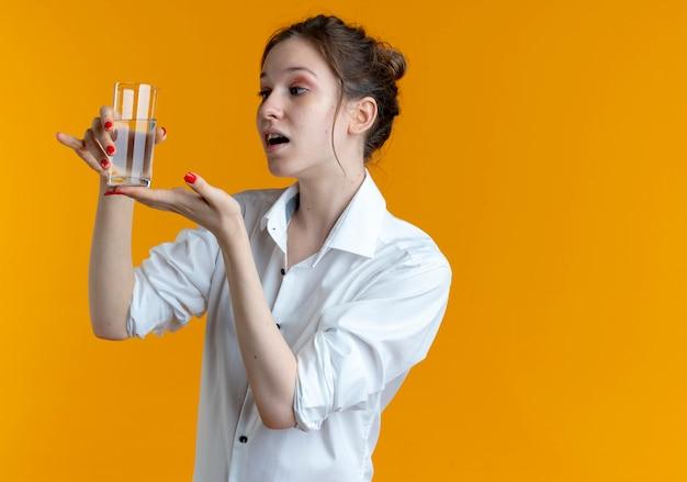 Junges überraschtes blondes russisches mädchen hält und zeigt auf glas wasser auf orange mit kopienraum