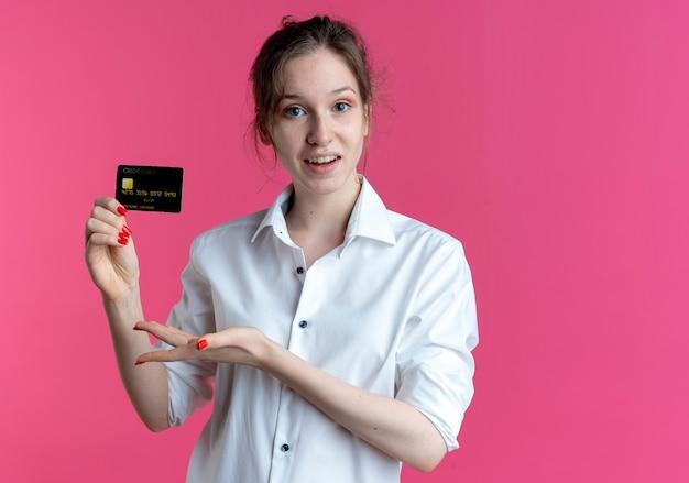 Junges überraschtes blondes russisches mädchen hält und zeigt auf kreditkarte