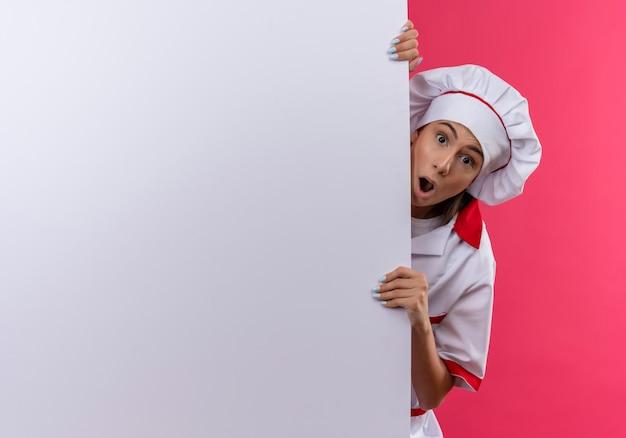 Junges überraschtes kaukasisches kochmädchen in der kochuniform steht hinter weißer wand auf rosa mit kopienraum
