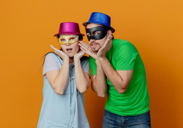 Junges überraschtes paar, das rosa und blaue hüte trägt, setzte maskerade-augenmasken auf, die hände auf kinn lokalisiert auf orange wand setzen