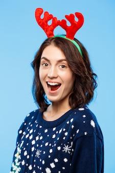 Junges überraschtes schönes brünettes mädchen im gestrickten pullover und im weihnachtsrentiergeweih, das über blaue wand lächelt