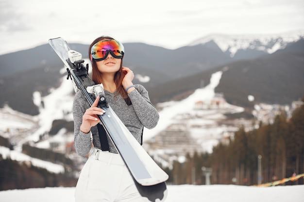 Junges und aktives brünettes skifahren. frau in den schneebedeckten bergen.