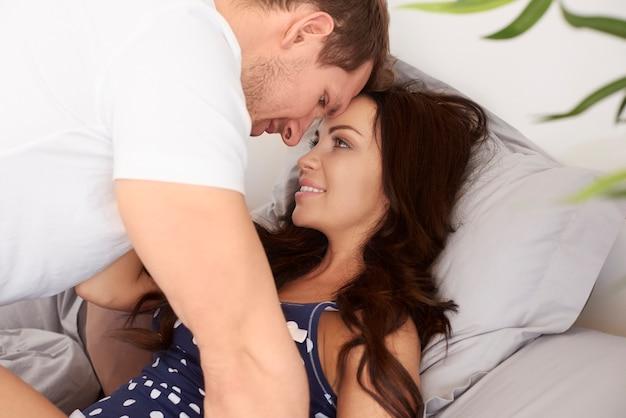 Junges und attraktives paar, das zeit zusammen im bett verbringt