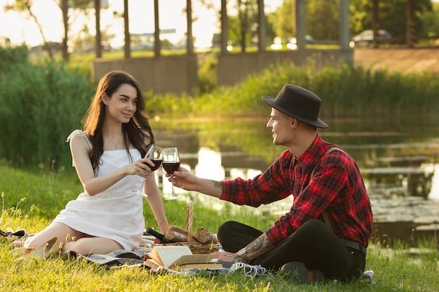 Junges und glückliches paar, das ein picknick am park am sommertag genießt