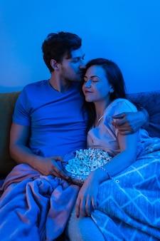 Junges und glückliches paar, das popcorn isst und film schaut