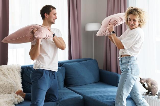 Junges und glückliches paar während der kissenschlacht in ihrer wohnung