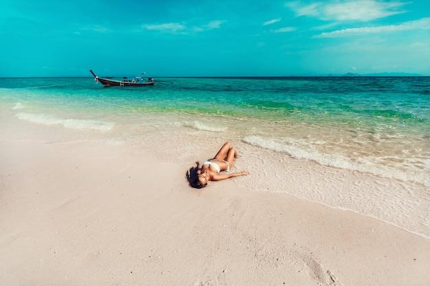 Junges und hübsches mädchenmodell in einem bikini, der auf dem strandurlaubsort der andamanensee ein sonnenbad nimmt