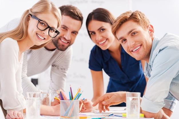 Junges und kreatives team. vier fröhliche geschäftsleute in eleganter freizeitkleidung diskutieren etwas und lächeln, während sie sich am tisch lehnen