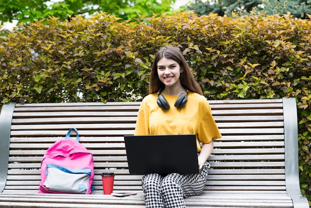 Junges und schönes kaukasisches mädchen mit kopfhörern, das auf einer bank sitzt, einen laptop benutzt und in die kamera schaut