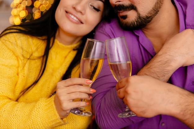 Junges und schönes paar, das am tisch mit gläsern des champagners sitzt, der in der liebe glücklich ist, weihnachten zusammen im weihnachtlich dekorierten raum mit weihnachtsbaum im hintergrund zu feiern