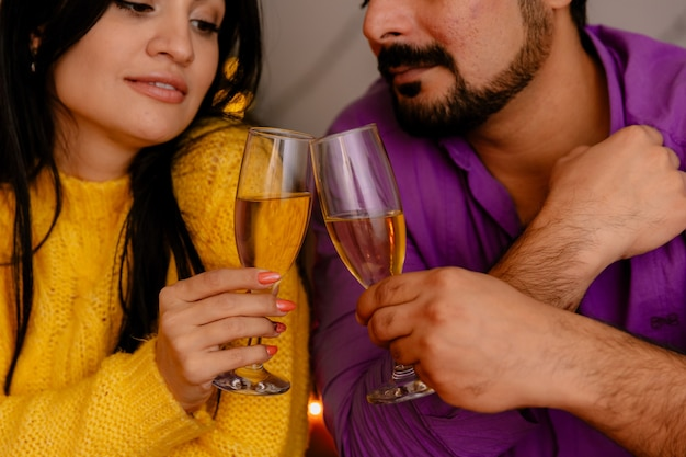 Junges und schönes paar, das am tisch mit gläsern des champagners sitzt, der in der liebe glücklich ist, weihnachten zusammen im weihnachtlich geschmückten raum mit weihnachtsbaum im hintergrund zu feiern