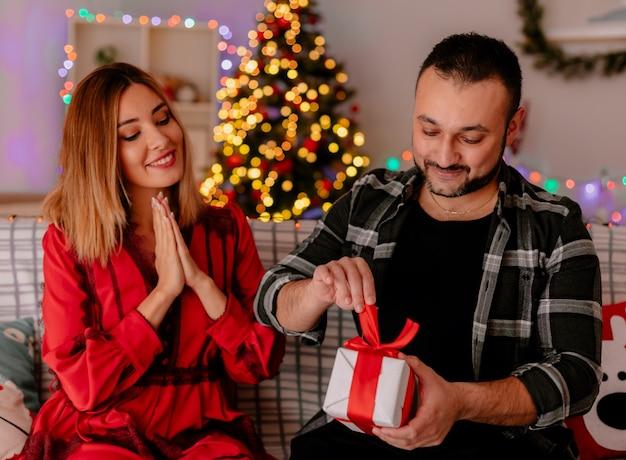 Junges und schönes paar, das auf einem couch-mann sitzt, der ein geschenk öffnet, während seine glückliche freundin ihn betrachtet, die weihnachten zusammen im geschmückten raum mit weihnachtsbaum im hintergrund feiert