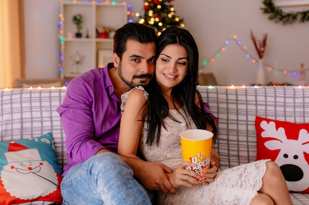 Junges und schönes paar, das auf einer couch mann und frau mit eimer popcorn sitzt zusammen fernsehen glücklich in der liebe in dekoriertem raum mit weihnachtsbaum im hintergrund