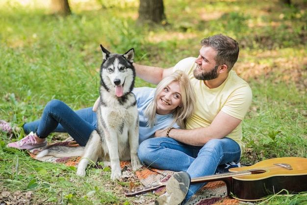 Junges und schönes paar entspannen in der natur mit einem hund zur gitarre