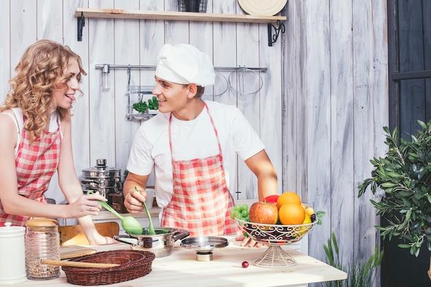 Junges und schönes paar in der küche kochen zu hause und frühstücken zusammen und helfen sich gegenseitig
