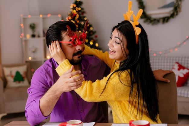 Junges und schönes paar mann und frau, die am tisch mit keksen sitzen, die spaß zusammen glücklich in der liebe im weihnachtlich geschmückten raum mit weihnachtsbaum im hintergrund haben