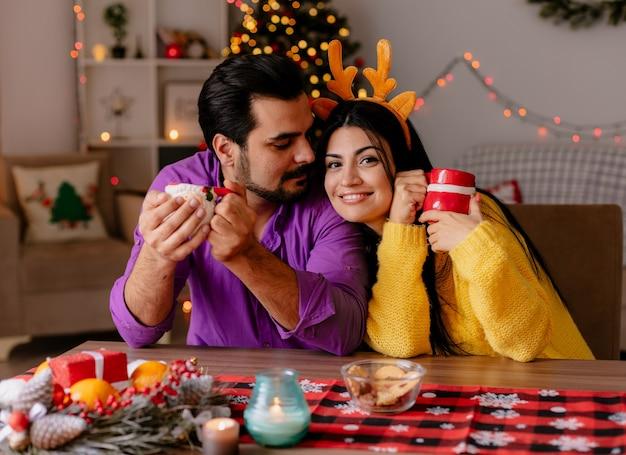Junges und schönes paar mann und frau, die am tisch mit tassen tee glücklich in der liebe im weihnachtlich geschmückten raum mit weihnachtsbaum im hintergrund sitzen