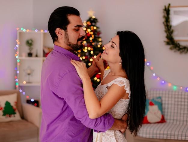 Junges und schönes paar mann und frau glücklich in der liebe tanzen in weihnachten dekorierten raum mit weihnachtsbaum im hintergrund