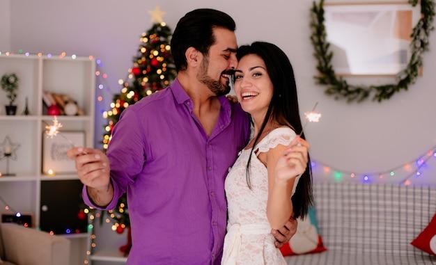 Junges und schönes paar mann und frau mit wunderkerzen, die nebeneinander glücklich in der liebe stehen, die weihnachten zusammen im geschmückten raum mit weihnachtsbaum im hintergrund feiert