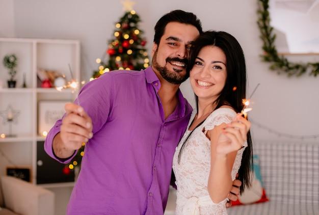 Junges und schönes paar mann und frau mit wunderkerzen umarmt glücklich in der liebe, die weihnachten zusammen im geschmückten raum mit weihnachtsbaum im hintergrund feiert