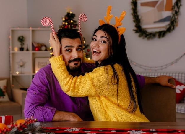 Junges und schönes paar mann und frau mit zuckerstangen, die spaß zusammen glücklich in der liebe in weihnachtlich geschmücktem raum mit weihnachtsbaum im hintergrund haben