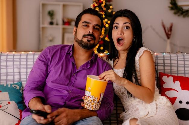 Junges und schönes paar überraschte frau und glücklichen mann, der auf einer couch mit eimer popcorn sitzt, der zusammen im dekorierten raum mit weihnachtsbaum im hintergrund fernsieht