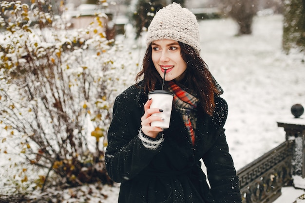 Junges und stilvolles mädchen im schwarzen mantel und in trinkendem kaffee des weißen hutes in der winterstadt