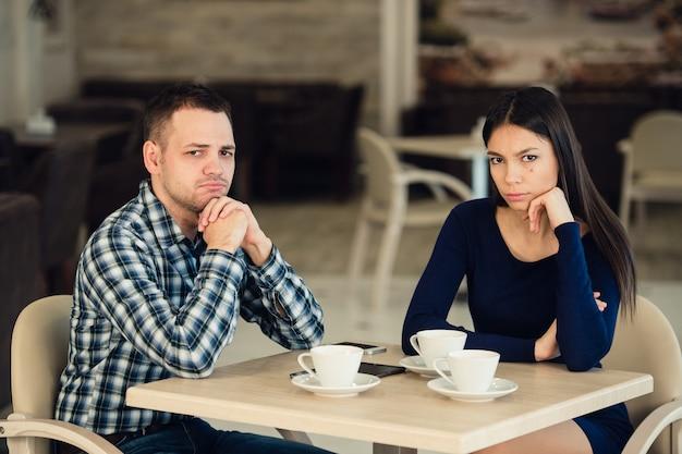 Junges unglückliches paar, das in einem café kämpft