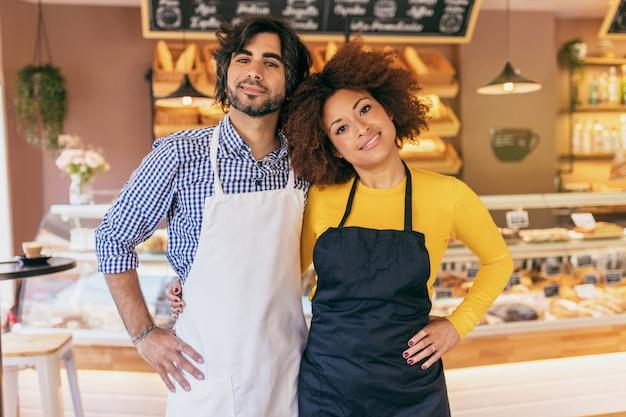 Junges unternehmerpaar, sie haben gerade ihre bäckerei eröffnet.