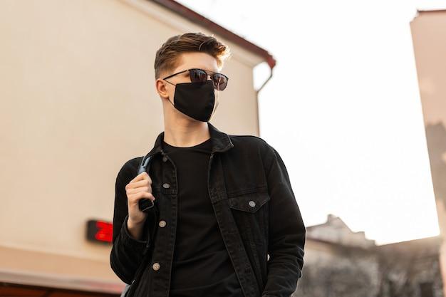 Junges urbanes stilvolles mannmodell in modischer schwarzer jeansjacke mit rucksack in vintage-sonnenbrille