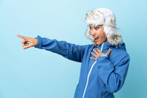 Junges uruguayisches mädchen mit wintermütze lokalisiert auf blauem hintergrund, der finger zur seite zeigt